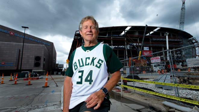 Longtime Milwaukee Bucks season ticket holder Roger Quindel is shown Monday outside the BMO Harris Bradley Center and the new arena for the Bucks. Quindel was a little shocked by the jump in ticket prices.