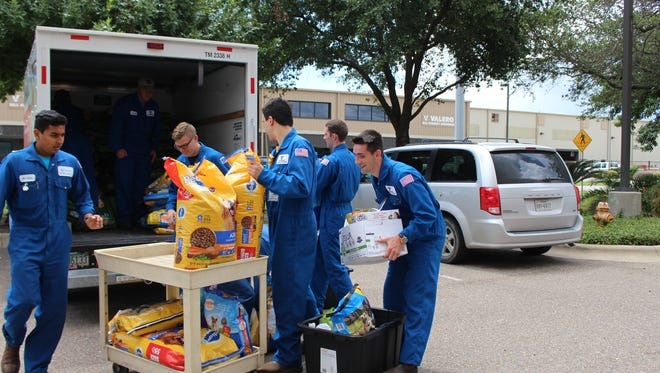 Valero employees load pet food donated for area shelters.