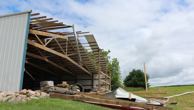 A wall damaged by a tornado sits on the ground Friday at a farm in Portage County.