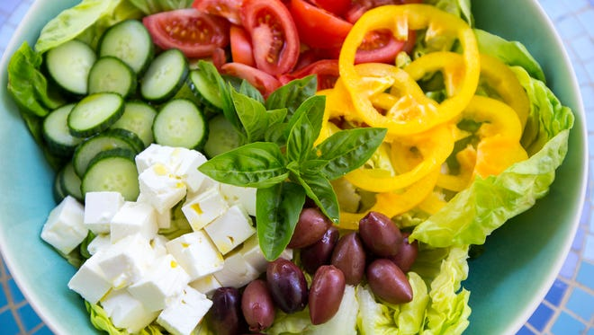 Enquirer food writer Polly Campbell presents a Greek Salad at her home in the Pleasant Ridge neighborhood of Cincinnati on Monday, July 17, 2017. Fresh basil tops the non-traditional style Greek salad, fashioned after those you might find at Cincinnati style chili restaurants.