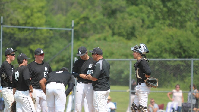 Greendale players congregate with manager Brian Johnsen during a pitching change July 17.