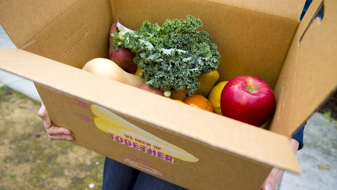 """Imperfect Produce spokesperson, Reilly Brock, holds an assembled customer box of """"ugly"""" fruits and vegetables."""