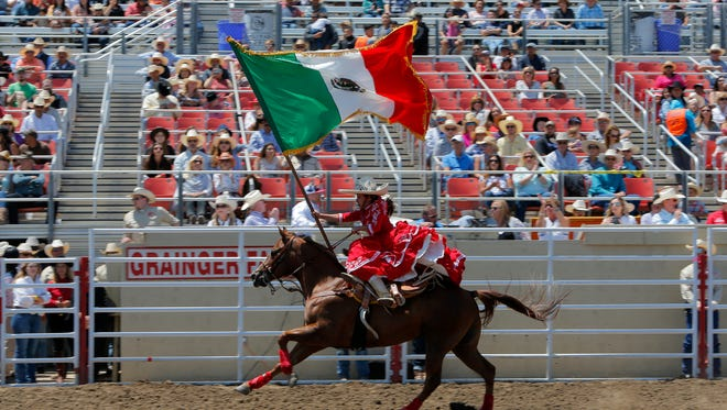 Daisey Barajas rides while waving the Mexican flag at the 107th California Rodeo Salinas on Sunday.