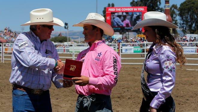 California Rodeo Salinsa President Mike Scarr shakes hands with competitor Clayton Biglow alongside Miss California Rodeo 2017 Lena Coulsen.