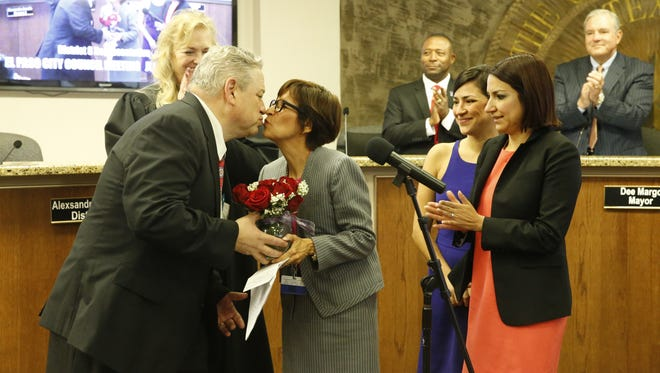 New city representative Cissy Lizarraga is congratulated with a kiss by her husband, 168th District Court Judge Marcos Lizarraga, after being sworn in to office Tuesday.