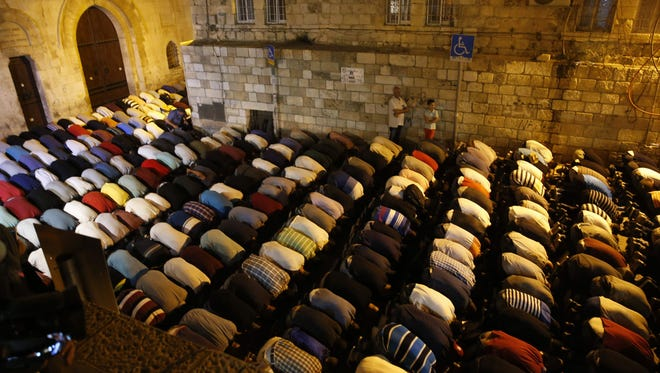 Palestinian Muslim worshipers pray outside Jerusalem's Old City on July 25, 2017, as Muslim officials said worshipers should continue to boycott the Al-Aqsa mosque compound, even after Israel removed newly installed security measures that had triggered deadly violence.