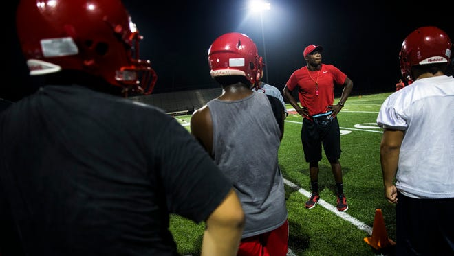 Immokalee head coach Rodelin Anthony surveys his team before drills begin at the first practice of the season at Immokalee High School on Monday, July 31, 2017. The Immokalee football team exceeded expectations in AnthonyÕs first season as a head coach last year, making it all the way to the regional championship game.