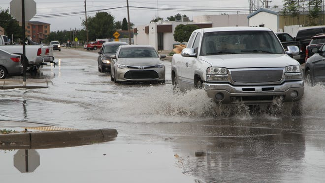 Cars drive through water-filled intersection of Greene and Halagueno streets, Tuesday, Aug. 1, 2017. The flooded intersection was a result of a thunderstorm Monday night. National Weather Service reported five to six inches of rain from the storm.