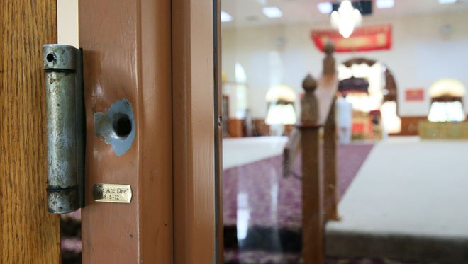"""A bullet hole left from the Aug. 5, 2012, attack on the Sikh Temple of Wisconsin remains next to a hinge on the door to the main hall. Beneath the hinge is a small brass plate inscribed, """"We Are One"""" with the date, 8-5-12."""