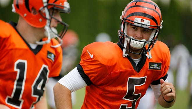 Cincinnati Bengals quarterback AJ McCarron (5) and quarterback Andy Dalton (14) warm up together before a practice at Bengals training camp at the Paul Brown Stadium practice facility in downtown Cincinnati on Monday, Aug. 7, 2017.