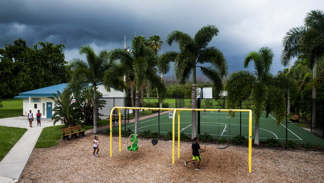 A thunderstorm rolls in as children run to the swing set at Anthony Park on Saturday, Aug. 5, 2017.
