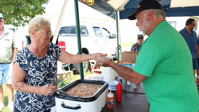 Shelby resident Bobbie Mack, left, serves ham and bean soup to Navy veteran Richard Herman in the veterans' tent at the Richland County Fair on Thursday. Herman was a fair board member for 21 years.