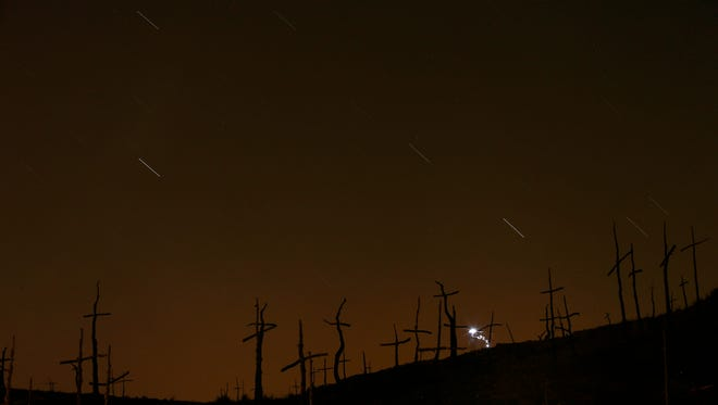 This Friday, Aug. 12, 2016 file photo made with a long exposure shows streaks in the sky during a Perseid meteor shower, seen behind crosses in Marganell, Spain. NASA's meteor expert, Bill Cooke, says astronomers are projecting a slightly higher than normal rate of 150 meteors per hour across North America. But the bright moon will wash out the finer Perseids. So the viewing rate will be more like 30 to 40 meteors an hour. Peak viewing will be Friday night, Aug. 11, 2017, early Saturday, Saturday night and early Sunday.
