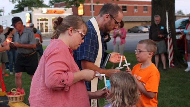Kattie Priebe and  John Priebe help their children Nehemiah, 9, and Joy, 5, light candles during a vigil in support of Charlottesville at the Christ United Methodist Church on Monday, Aug. 14, 2017. John Priebe is a co-pastor at the church.