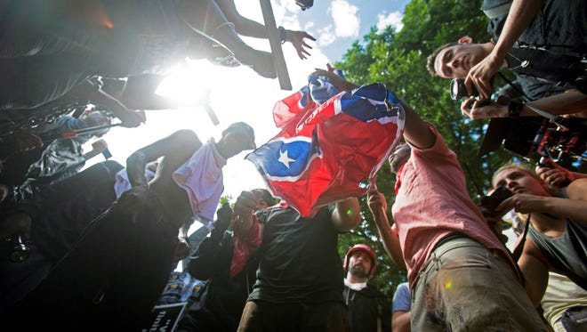 In this Aug. 12, 2017 file photo, counter-protesters tear a Confederate flag during a white nationalist rally in Charlottesville, Va. The deadly white nationalist demonstration in Virginia has brought new attention to an anti-fascist movement whose black-clad, bandana-wearing members have been a regular presence at protests around the country in the last year. Members of the antifa movement were among those protesting the Charlottesville rally last weekend. (Shaban Athuman /Richmond Times-Dispatch via AP, File)
