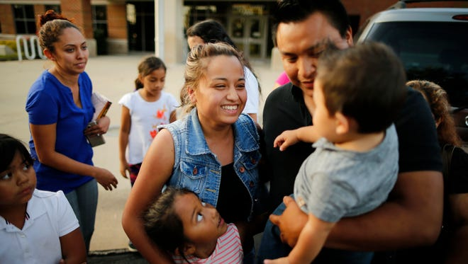 """""""Mi Amor,"""" says Riccy Enriquez Perdomo as she looks up to her 11-month-old son, Rony, while surrounded by family member as she's released from custody at the Boone County Jail in Burlington, Ky., on Thursday, Aug. 24, 2017. Riccy Enriquez Perdomo was released from county jail, after being arrested Aug. 17. Enriquez, had been granted legal status two times through DACA (Deferred Action for Childhood Arrivals) but was arrested at an immigration office in Louisville. She had gone there to post bond for another immigrant being held who was eligible for release."""
