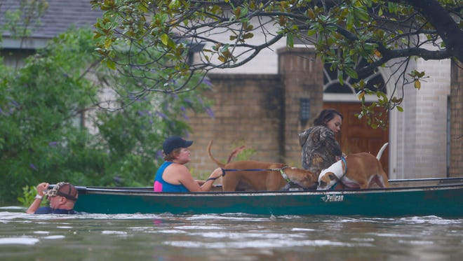 A family evacuates their Meyerland home in Houston on Aug. 27, 2017, amid rising floodwaters.