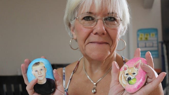Artist Roberta Kirby holds up two memorial rocks she has painted for grieving families.