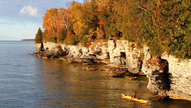 A kayaker paddles along Cave Point County Park in Door County.