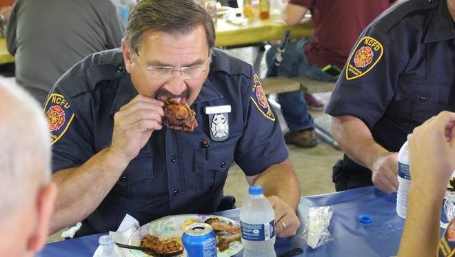 City of Northville Firefighter (serving Plymouth) Dave Tabaka enjoys some of Chef Paul Penney's famous barbequed chicken.  Tabaka also is a Plymouth resident.
