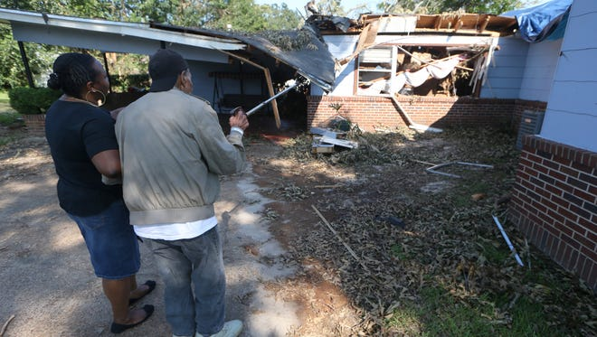 Hodges Abner uses his cane to point out some of the damage to his home, to his granddaughter Jamye Brown. The Abner's home was struck by a large tree, falling during Hurricane Hermine last year.