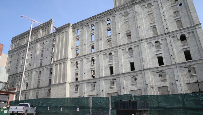 Work has stopped on converting the former Pabst malt house into upscale apartments. But the developer says a new cash infusion will help renovations soon resume.