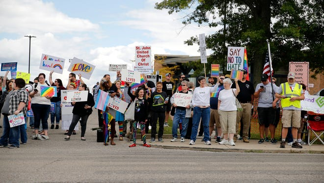 Counter-protesters demonstrate against Westboro Baptist Church in front of Oak Hills High School, Wednesday, Sept. 6, 2017, in Green Township, Ohio.