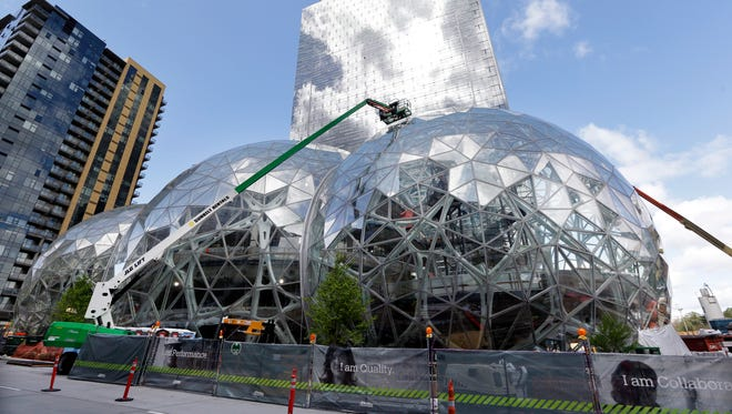 "FILE - In this April 27, 2017 file photo, construction continues on three large, glass-covered domes as part of an expansion of the Amazon.com campus in downtown Seattle. Amazon said Thursday, Sept. 7,  that it will spend more than $5 billion to build another headquarters in North America to house as many as 50,000 employees. It plans to stay in its sprawling Seattle headquarters and the new space will be ""a full equal"" of its current home, said founder and CEO Jeff Bezos. (AP Photo/Elaine Thompson)"