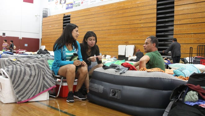 Miami evacuee Gloria Llerena (left), 41, talks with her daughter, Michelle Saavedra, 19, and her husband at a Red Cross shelter at Lawton Chiles High School Saturday before Hurricane Irma.
