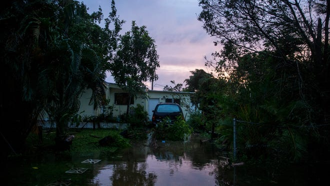 Downed trees and floodwater cover a driveway on Sunray Drive in Bonita Springs after Hurricane Irma passed through on Sunday, Sept. 10, 2017.