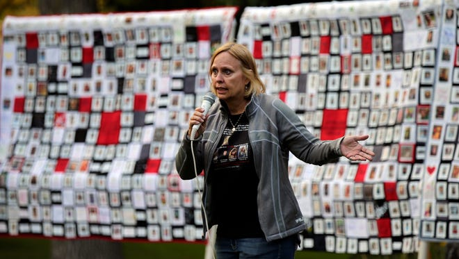 Bev Kelley-Miller speaks Sunday in front of three quilts showing the Wisconsin faces of addiction and recovery during the Fox Cities Lights of Hope gathering at City Park in Appleton.