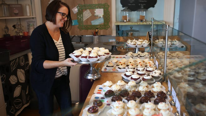 Lucy & Leo's Co-owner Paula Lucas puts out cupcakes at the cupcakery's storefront on Thomasville Road Thursday.