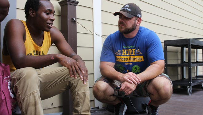Shane Johnson, a U.S. Marine Corps veteran who is hiking across the country to raise awareness about his nonprofit BOOYAH Veteran Bus Project, speaks with Kearney Center resident Catherine Williams' son, Terry Richmond, Jr. His grandfather was a Vietnam War veteran.