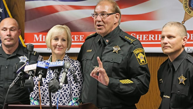 Milwaukee County Acting Sheriff Richard Schmidt, with his wife, Valori (left), at his side, announces he will seek interim appointment to the job.