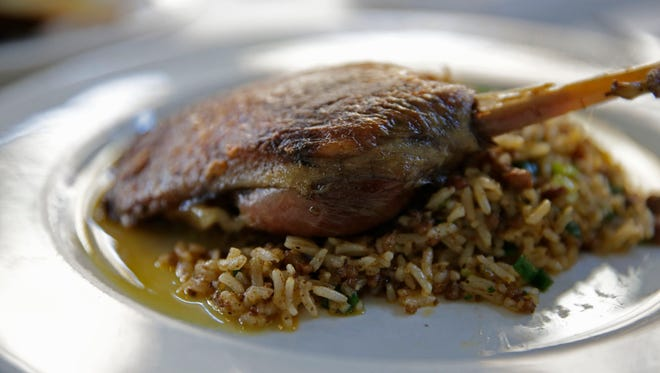 Dirty rice, shown here with duck confit at Herbsaint in New Orleans, is a Cajun classic.