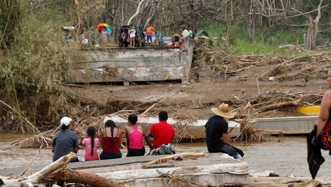 People sit on both sides of a destroyed bridge that crossed over the San Lorenzo de Morovis River, in the aftermath of Hurricane Maria, in Morovis, Puerto Rico, on Sept. 27, 2017.