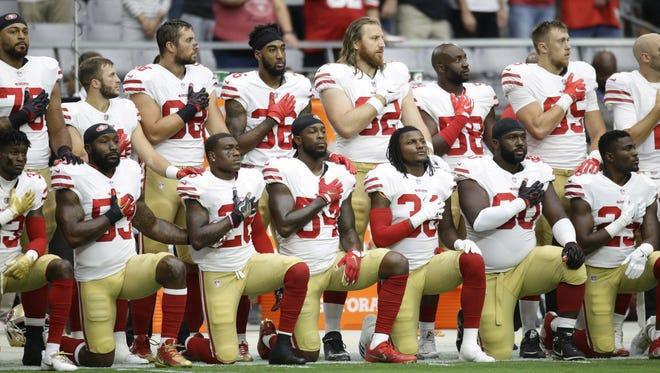San Francisco 49ers kneel during the national anthem on Oct. 1, 2017 at University of Phoenix Stadium in Glendale, Ariz.