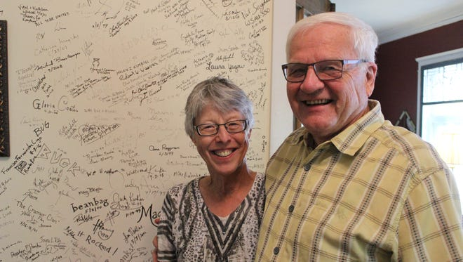 Lori and Dave Torkko stand in front of the wall of fame, which guests get to sign after a stay at the Everest Inn.