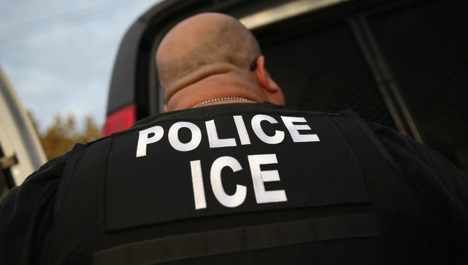 In this file photo, a U.S. Immigration and Customs Enforcement (ICE), agents detain an immigrant in Los Angeles.