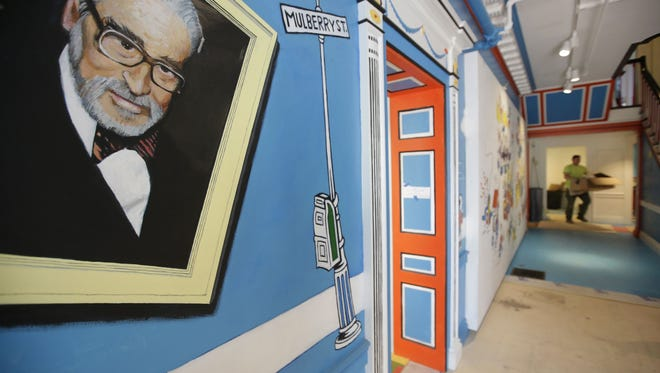 A mural features Theodor Seuss Geisel, left, also know by his pen name Dr. Seuss, near an entrance at The Amazing World of Dr. Seuss Museum, in Springfield, Mass. The museum is removing controversial images from a mural because they are considered racist.