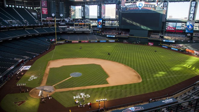 The field gets freshly cut as paint is applied to new NLDS logos the day before Game 3 at Chase Field in Phoenix, Ariz. on October 8, 2017.