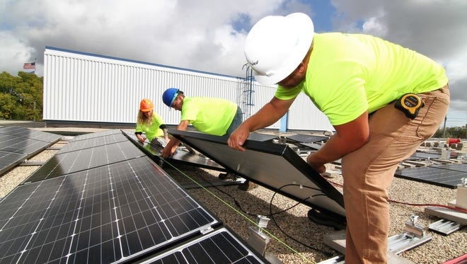 Alyssa Martinez (from left), Jace Olson and Matt Webber, all from EcoPower, install solar energy panels onto racking supports on the roof of Badger Meter Inc. in Brown Deer. EcoPower is a Madison-based solar installation company. The solar system is projected to offset 11% of Badger Meter's energy costs annually.