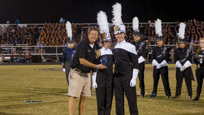 The Ravenwood Band drum majors accept the Grand Champion trophy for the Sonic Boom High School Marching Band Competition from Franklin's Band Booster Board President, Ron Whitler