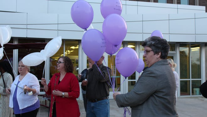 Domestic Violence Shelter executive director Kathy Ezawa passes out balloons during a candlelight vigil Thursday, Oct. 19, 2017. October is Domestic Violence Awareness Month.