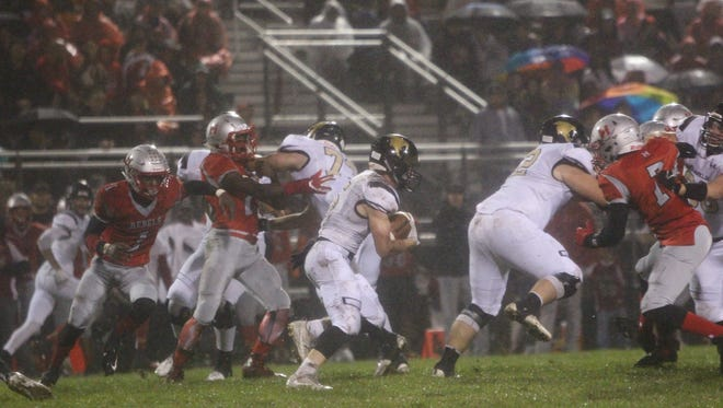 With Josh Narrai (left) and Jake Gannon leading the way, Franklin running back Brad Tobin heads toward a hole against Racine Horlick earlier this year.