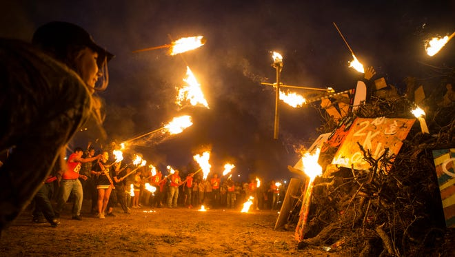 Refugio seniors throw their torches to ignite the homecoming bonfire on Wednesday, Oct. 25, 2017.