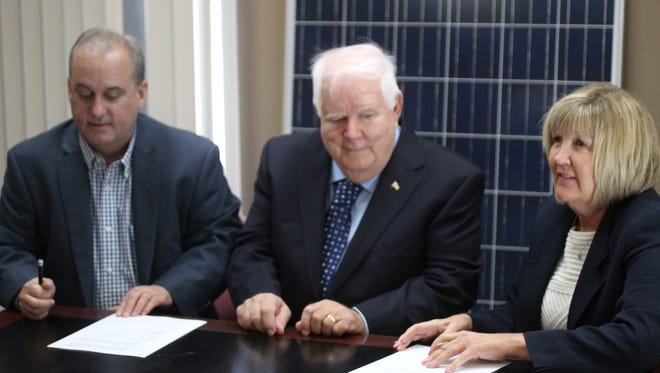 Jeff Whitney, managing director of IntriEnergy, William Boyle, CEO of Solar Connection and Jackie Coffey, CEO of IntriEnergy, sign paperwork creating a solar technology joint venture that plans generate high efficiency, low cost, solar cells in Mars Hill.