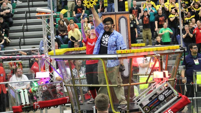 Raider Robotix pilot, Nihal Patel, holds up an extra gear collected after the red alliance won the match at the Mid Atlantic Regional Montgomery event in April 2017.