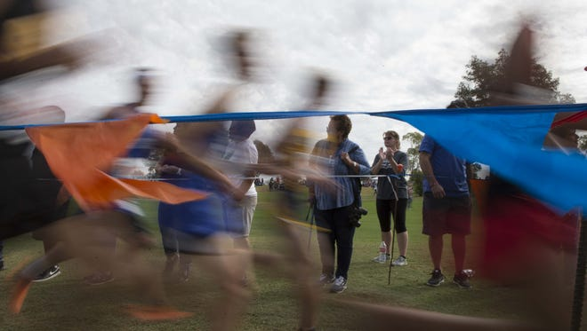Family and friends cheer to high school boys, and girls run during the State Cross Country Championships held at Cave Creek Golf Course on Nov. 4, 2017.