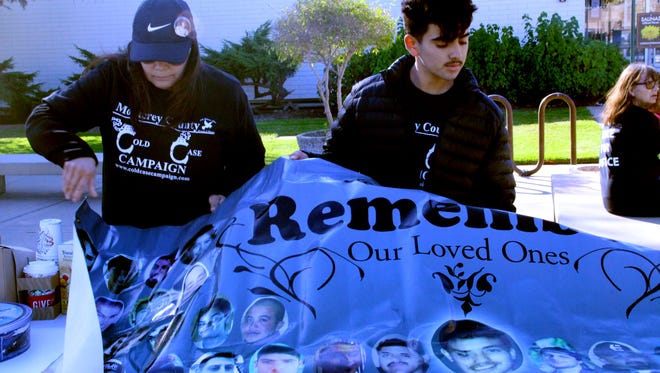FILE PHOTO: Virginia Gallegos, 56, and Christopher Aguilar, 16, unfurl a banner that shows the faces of more than 80 people lost to homicides in the Salinas area. Christopher Aguilar is the son of Debbie Aguilar, who organized a rally about cold cases. Christopher and Debbie Aguilar lost Stephen Aguilar in 2002. They haven't seen his killer brought to justice.